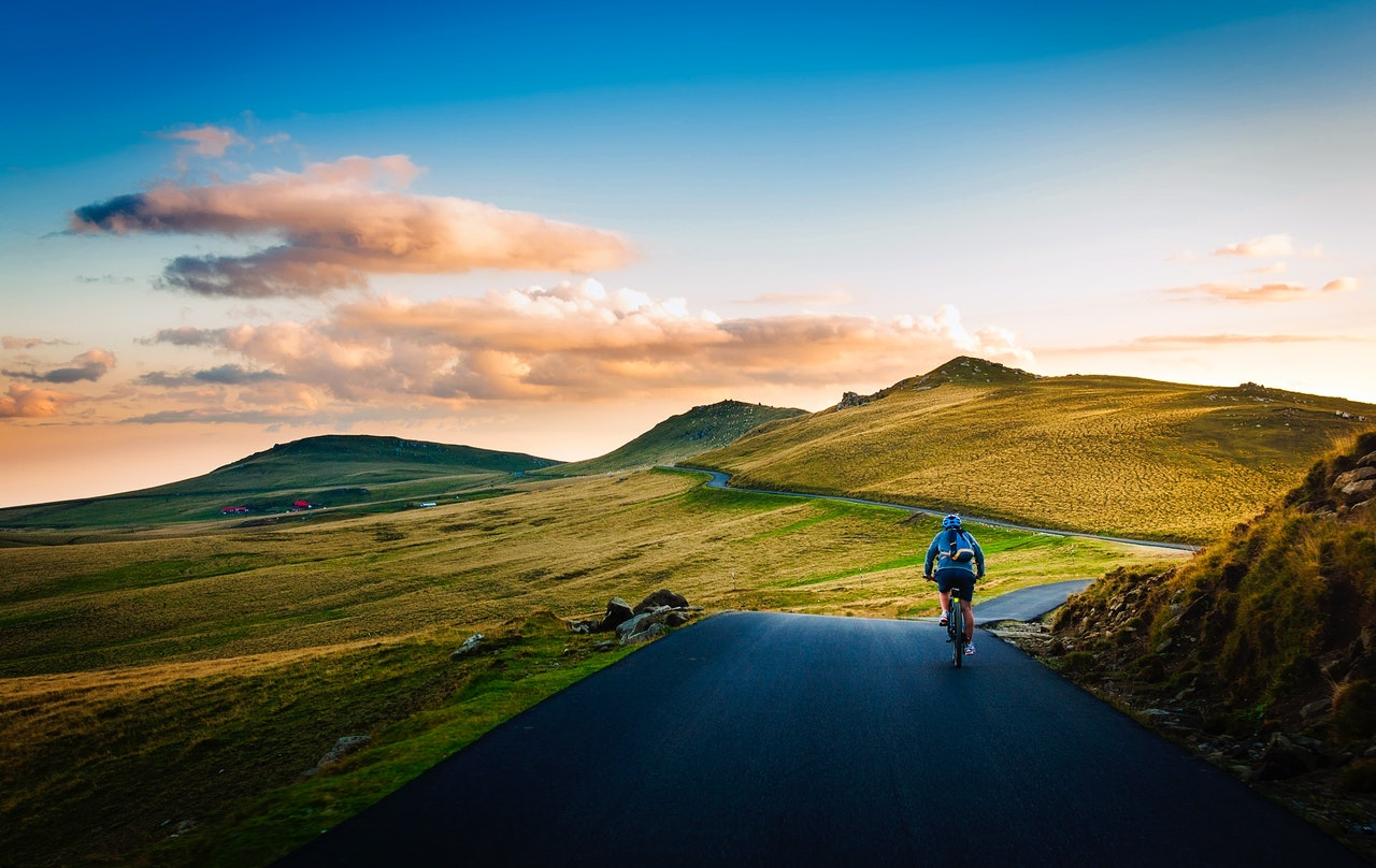 Migration to Kotest - a man on mountain road riding a bike towards rising sun